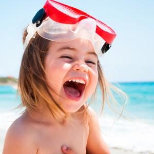 Bambina al mare con maschera che ride
